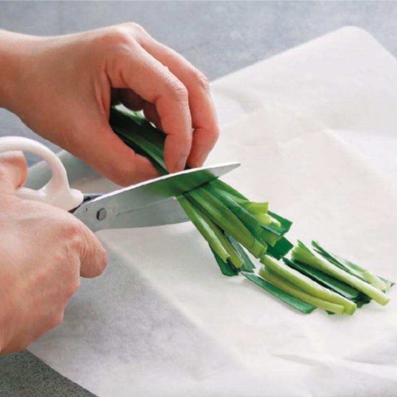 キッチンペーパーの上で、キッチンはさみを使ってニラを切っている