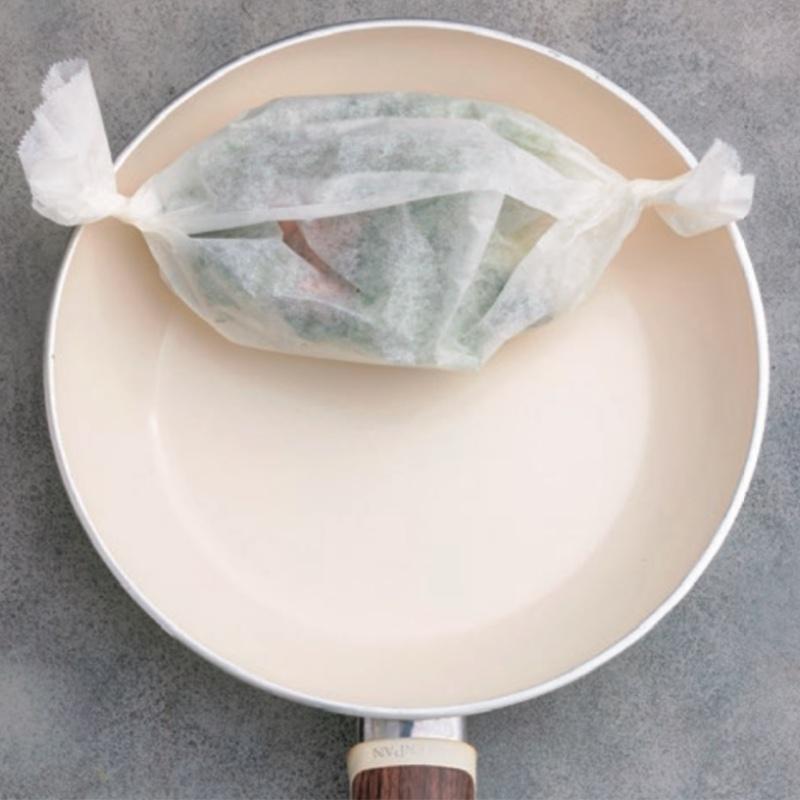 キッチンペーパーで包んだ素材をフライパンの上方に置いている