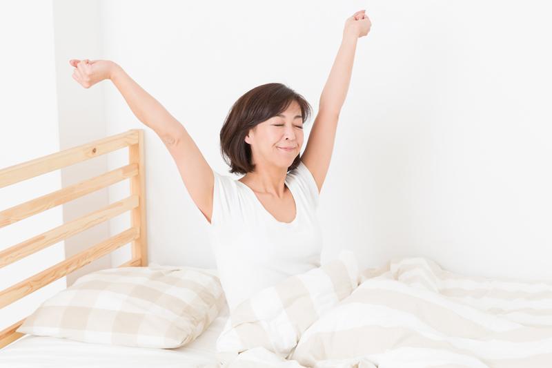 ベッドの上で気持ちよく目覚めている女性