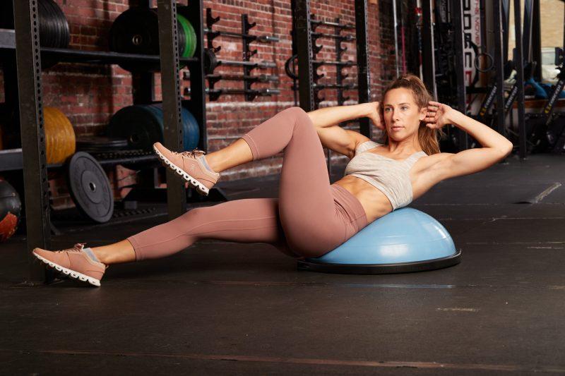 BOSU(ボス)バランストレーナー ホームバージョン 65cmの半円部分を上にして腹筋をしている女性