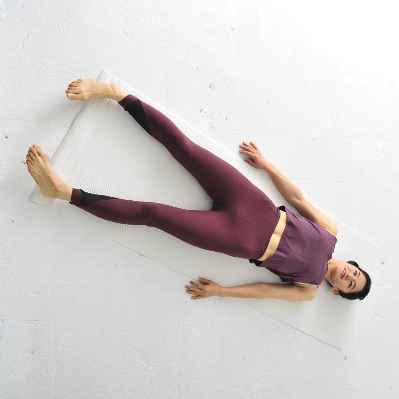 脚を開き、仰向けに寝転んでいる女性