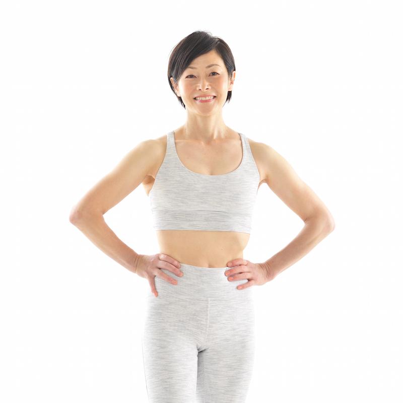 パーソナルトレーナーの池田佐和子さんが白のトレーニングウエアを着て、手を腰に置いて笑顔で立っている