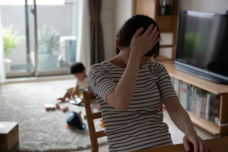 頭に手をやる女性と部屋で遊ぶ子供