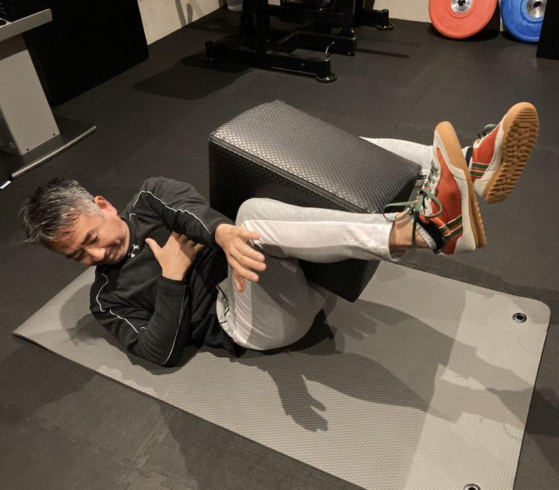 仰向け状態でFCB 50cmを両足ではさみ、左手を右膝のほうに伸ばしエクササイズをしている男性