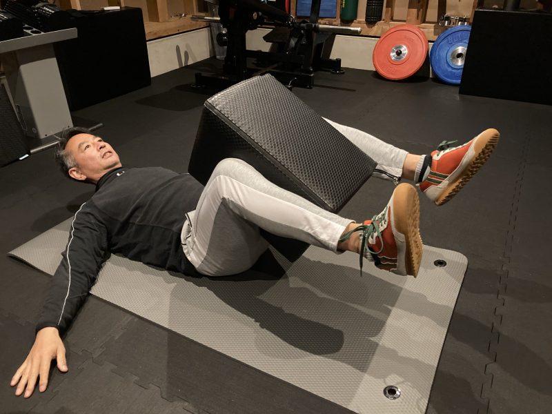 仰向け状態でFCB 50cmを両脚にはさみ頭と両足を浮かせている男性
