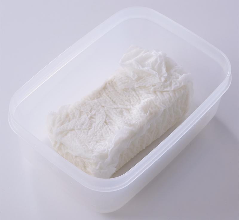 豆腐をキッチンペーパーで水切りして保存している