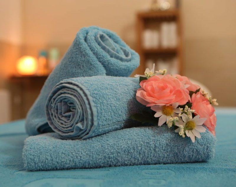たたんだタオルの上にくるくると巻かれたタオルが2つのせられ、花が添えられている