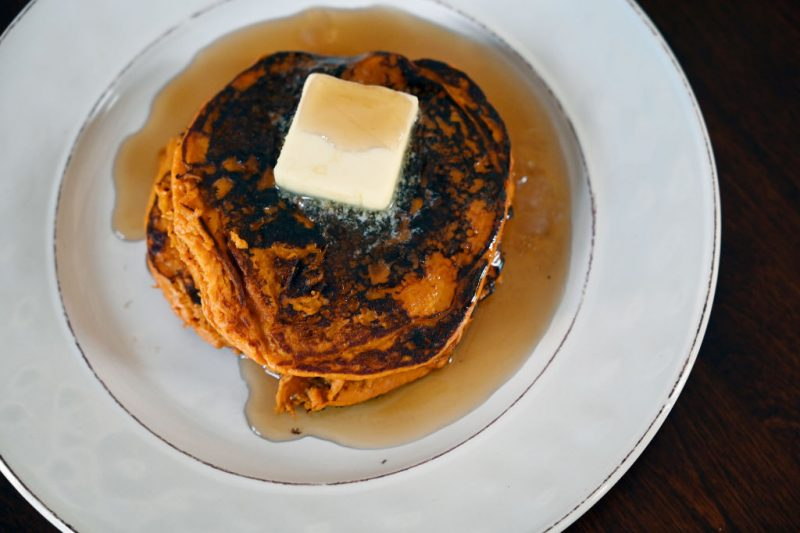 白い皿の上にのった焦げ目のついたホットケーキ上にバターがのって、メープルシロップがたっぷりかけられている
