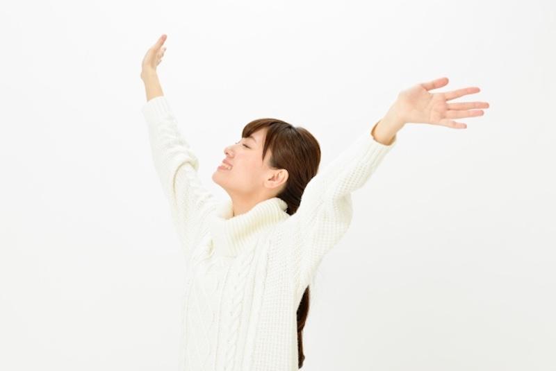 両手を大きく広げる女性