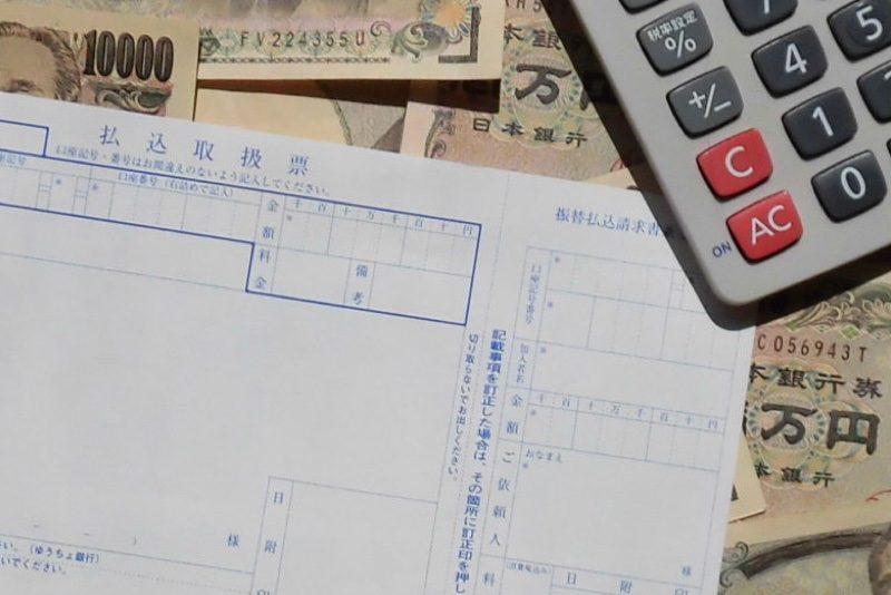 振込用紙とお金と電卓