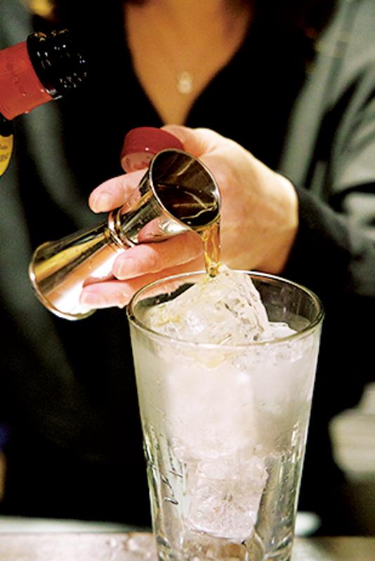 氷の入った冷えたグラスに、ウイスキーを入れている