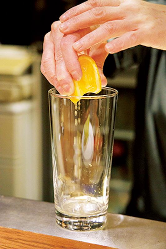グラスに柑橘を絞っている