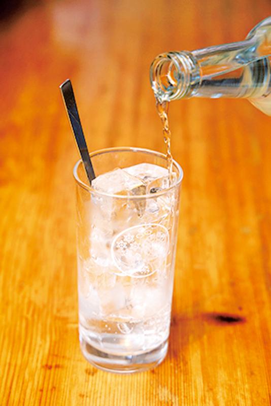 氷の入った冷えたグラスに焼酎を約1/4入れている