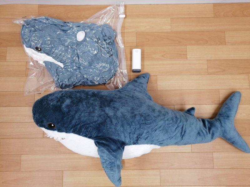 ハンディー衣類圧縮器『GOOD TRAVEL PLUS』で圧縮したいるかの抱きまくらと圧縮する前の同じイルカの抱きまくらを床に並べている