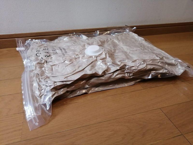 ハンディー衣類圧縮器『GOOD TRAVEL PLUS』で圧縮した毛布が床に置かれている