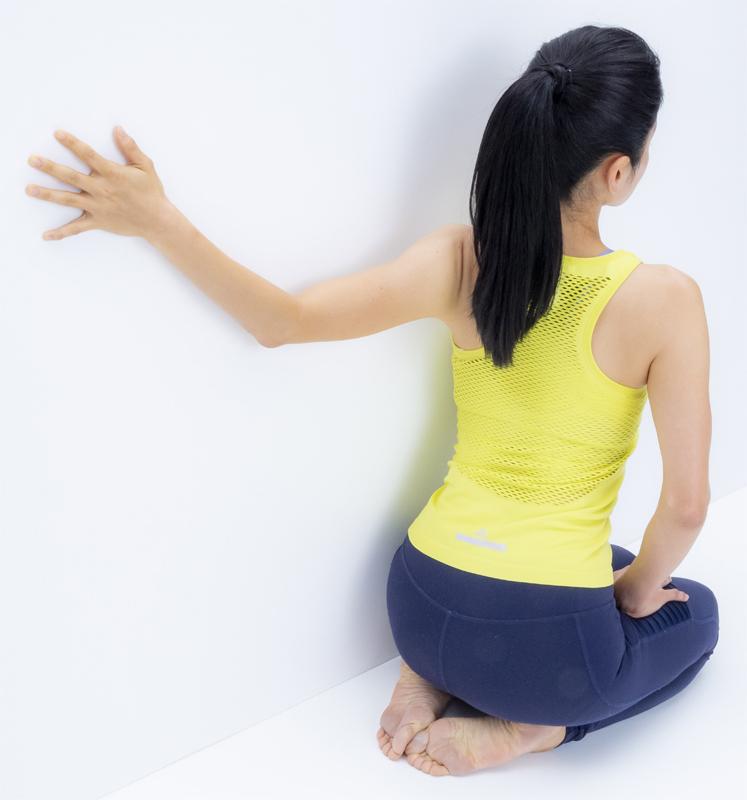 壁トレを後ろから見たところ。壁に体を預けるようにして、腕を回している
