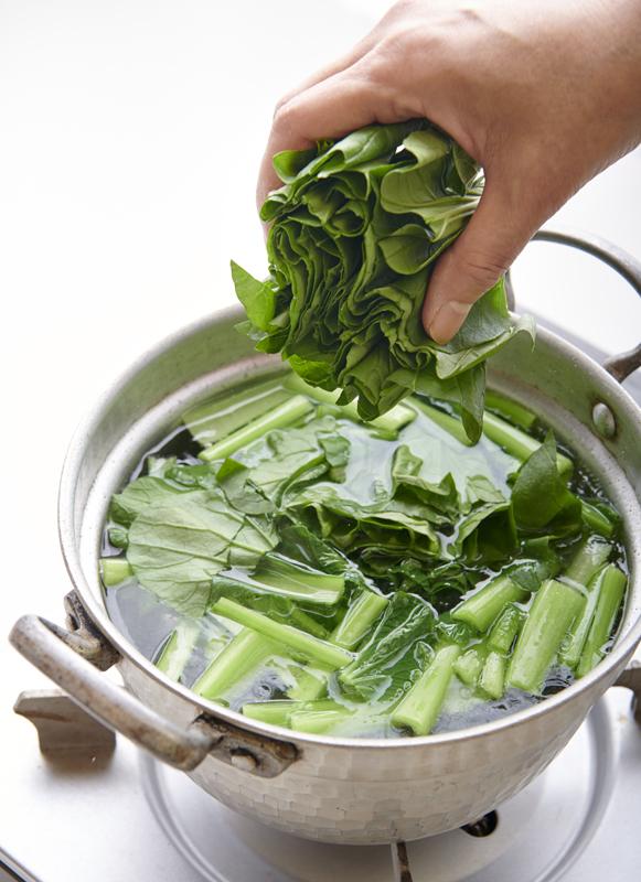 鍋に青菜を入れている