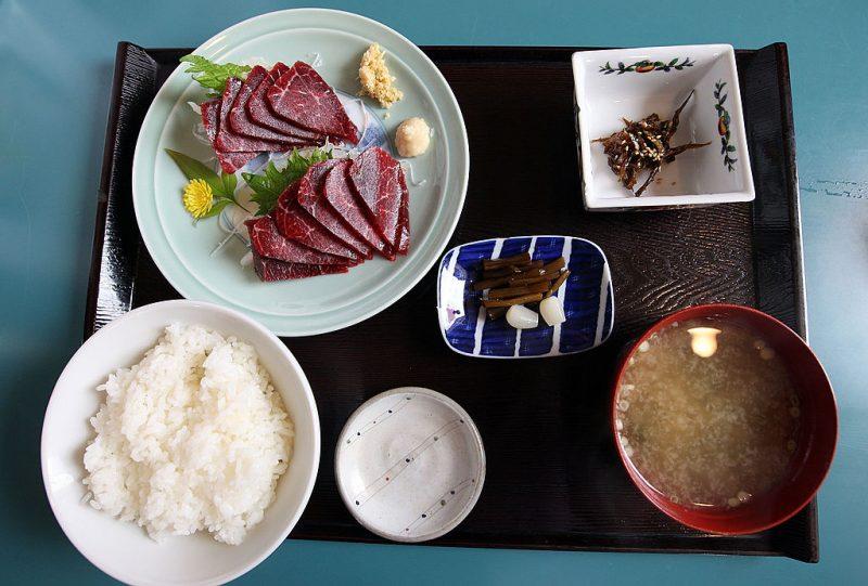 お盆に並べられた白米、お刺身、みそ汁小鉢などの定食