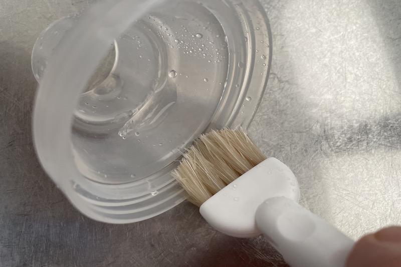 KEYUCAのすき間掃除シリーズ みぞ洗いブラシプラスチックの容器の蓋の細かいところを洗っている様子