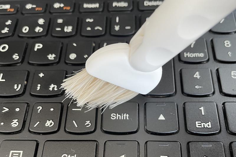 KEYUCAのすき間掃除シリーズ みぞ洗いブラシでパソコンのキーボードを掃除している手元