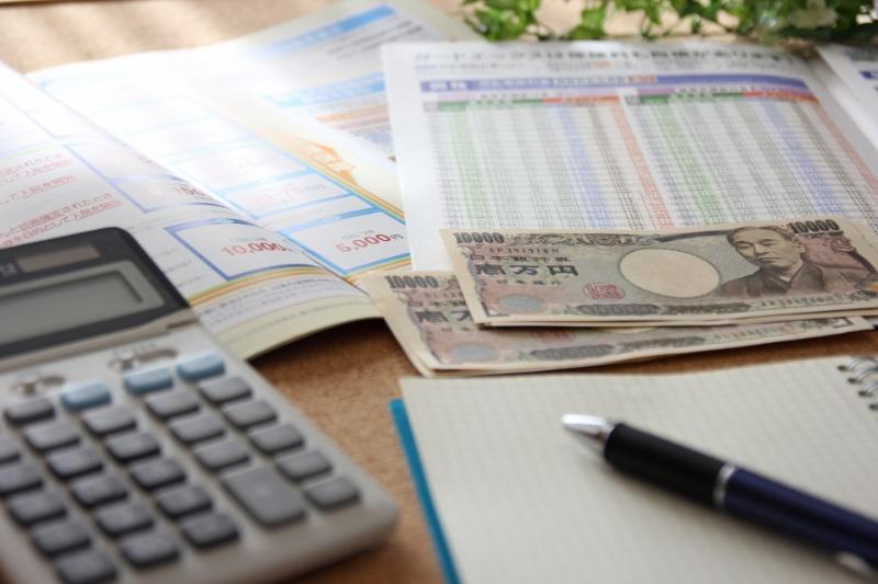 保険のパンフレットと電卓、お金、ペンとノート