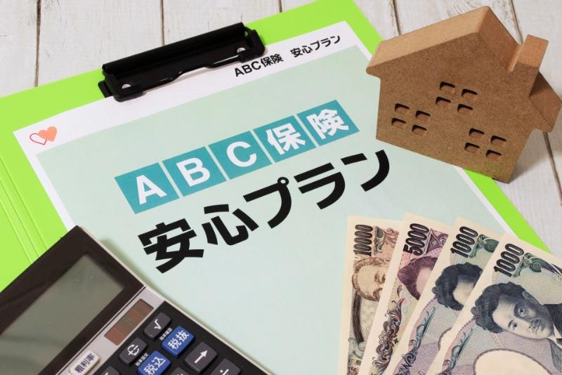 保険のパンフレットと電卓、お金