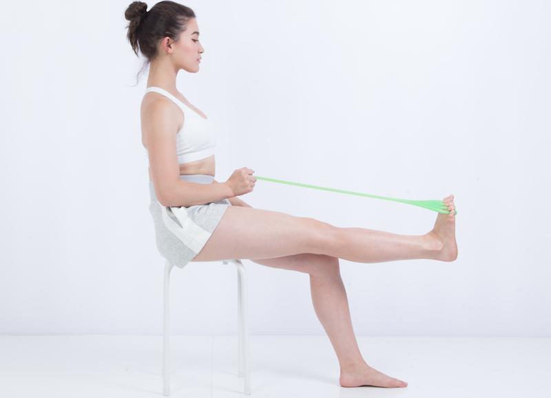 フロッグハンド ソフトタイプを趾にひっかけ脚のトレーニングをしている女性