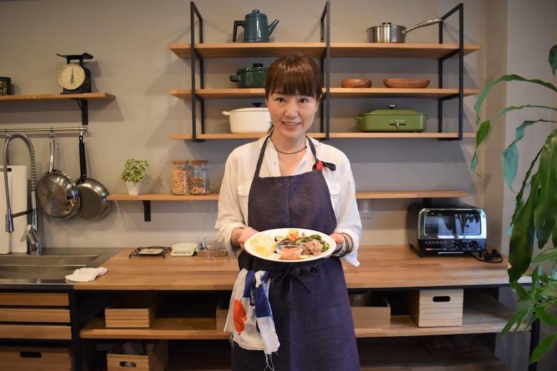 料理家の井上かなえさんが料理を盛った皿を両手で持ってキッチンに立っている