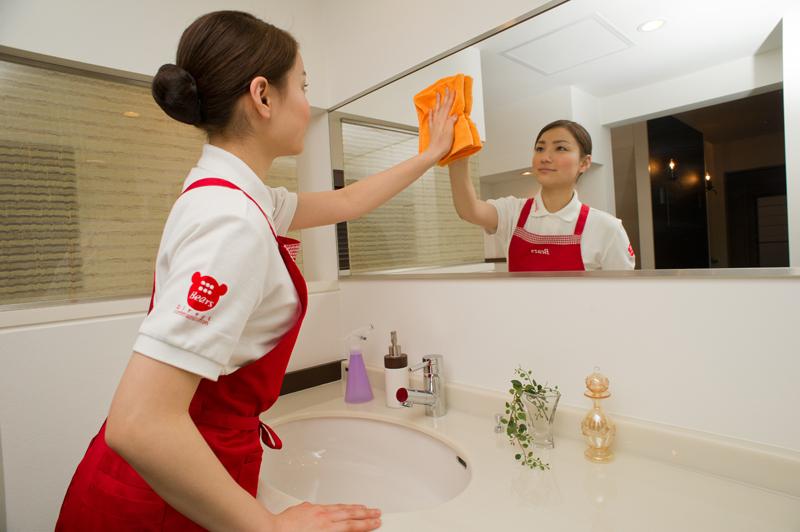 洗面所の鏡を拭く家事代行の女性