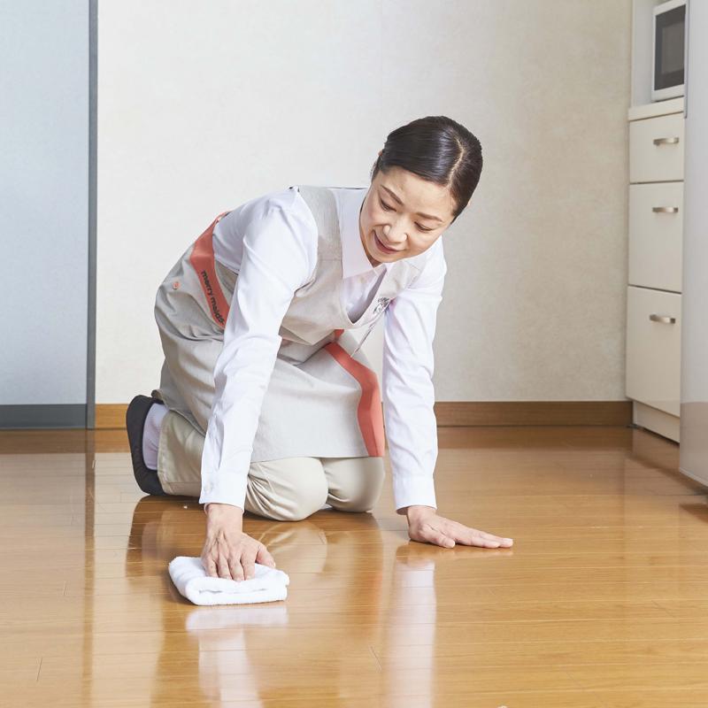 フローリングの床を拭く家事代行の女性