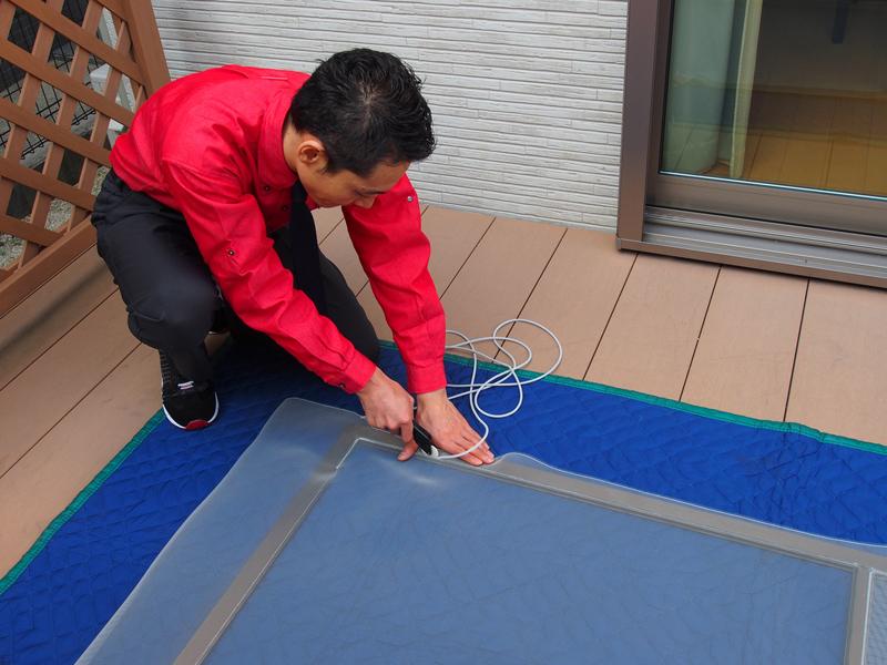 敷物の上にビニールカバーをかぶせて調整する家事代行の男性