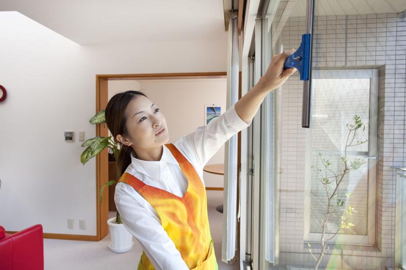ワイパーで窓拭きをする家事代行の女性