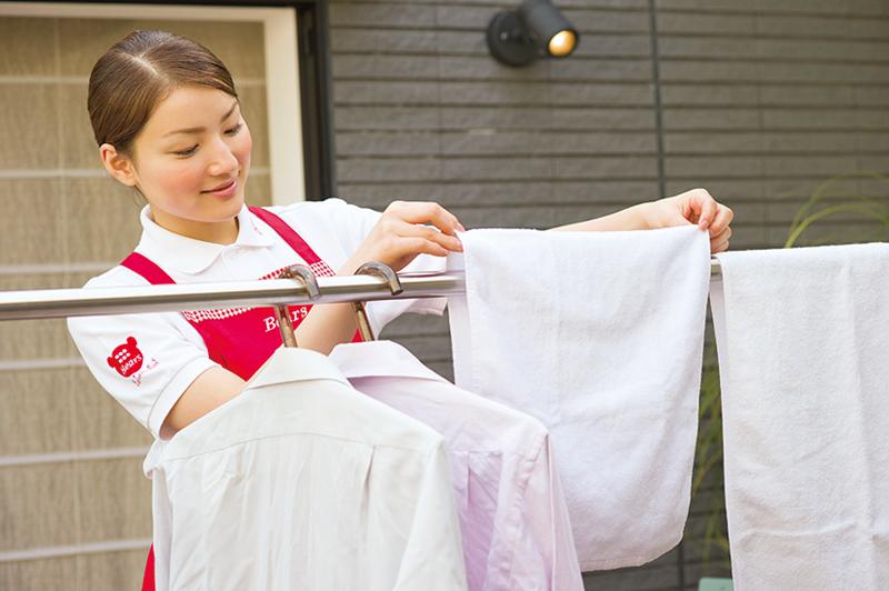 洗濯物を干す家事代行の女性