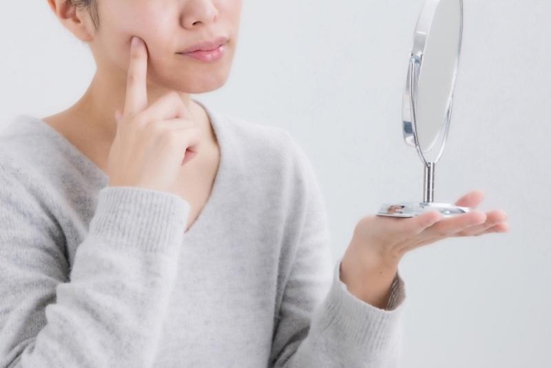 頬を触り、鏡を見る女性