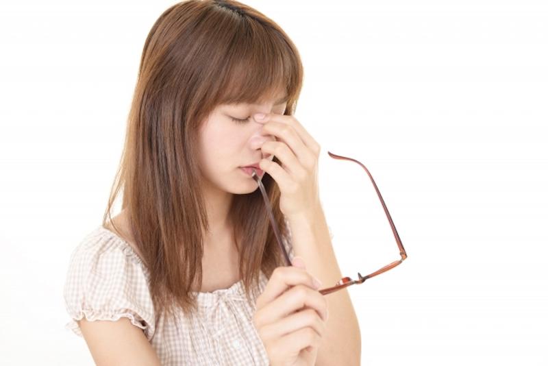 メガネを外し、目頭を押さえる女性