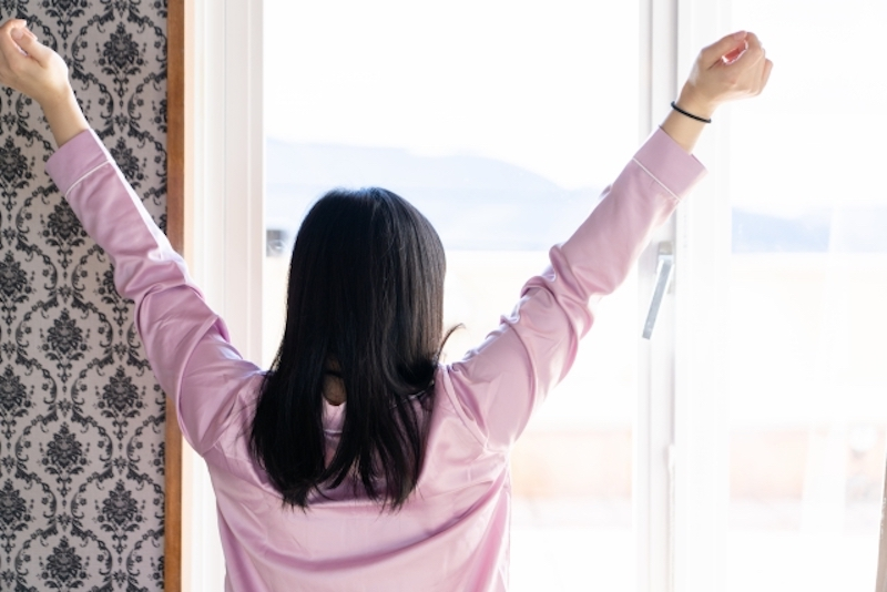 窓に向かって両腕を広げる女性