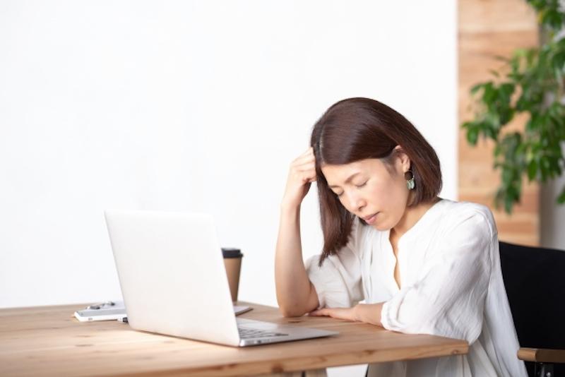 パソコンの前で頭に拳を当てる女性