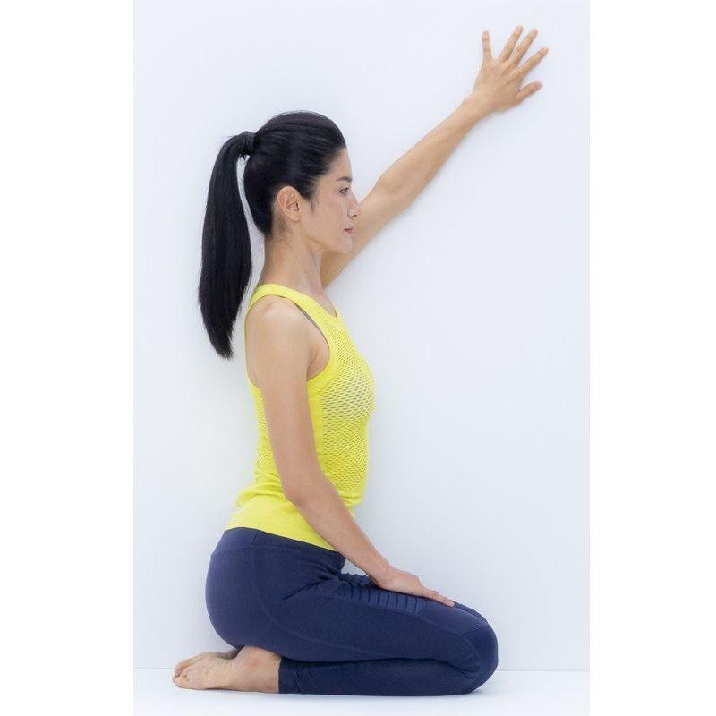 壁を左側にして正座し、左手をななめ上に伸ばして壁につけている
