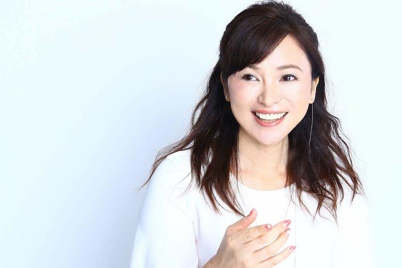 モデルの大佐古雅子さんがハーフアップのヘアスタイルで白い服を着て笑っている