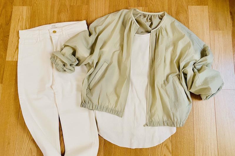 ユニクロのシアーコクーンブルゾンに白のインナーと白のデニムパンツが合わせて床に置かれている