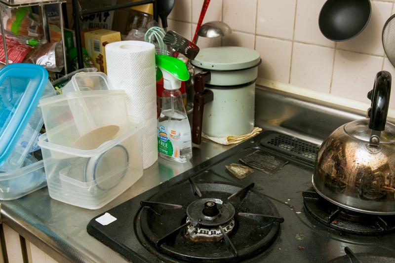 コンロの脇に積まれている保存容器や食品類