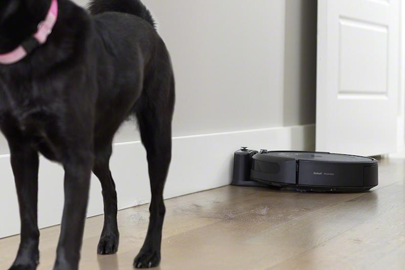 犬の後ろの床に落ちた犬の毛をアイロボット『ルンバi3+』が取ろうとしている様子