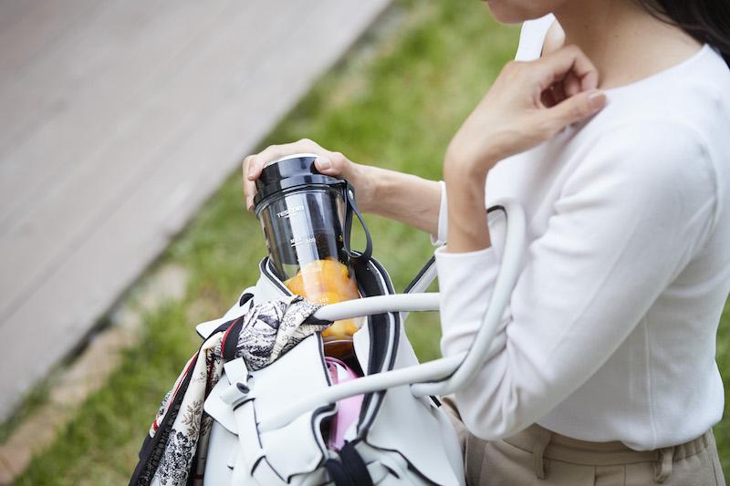 テスコム電機『コードレス タンブラーミキサー TMCX400』にオレンジのスムージーを入れてそれをバッグに入れている女性の手元