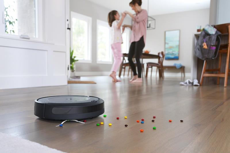 アイロボット『ルンバi3+』がリビングに落ちた細かいゴミを掃除している後ろで、女性と女の子が手をつなぎ合って踊っている
