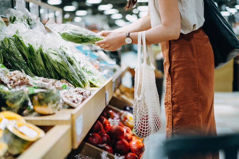 スーパーの野菜売り場で商品を選んでいる女性