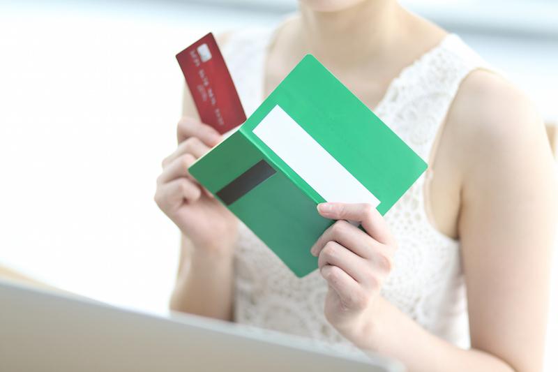 通帳とカードを手に持っている女性の手元