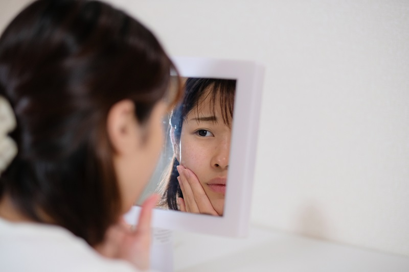 鏡を見ながら不機嫌そうな女性