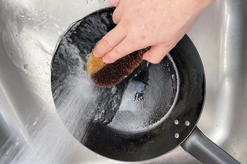 亀の子束子 ハーフハードで鉄のフライパンをこすり洗いしている手元
