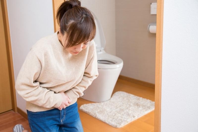 トイレの前でお腹を押さえる女性