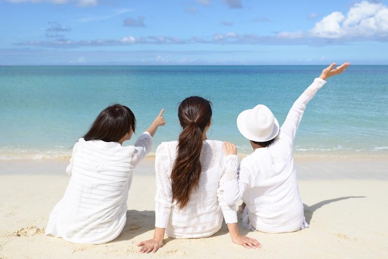 砂浜に座って海を見る3人の女性